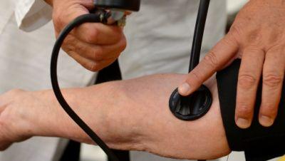 arzt misst bei einer patientin den blutdruck
